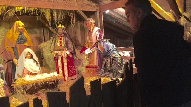 A local Nativity scene with the baby Jesus at the center of an adoring crowd.