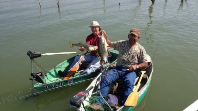 Fishermen show off two large Twin Buttes Reservoir black bass. The reservoir continues to offer rewarding sports fishing as it recovers from a prolonged drought.