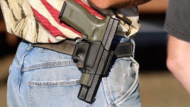 A man openly carries a handgun at a public event.