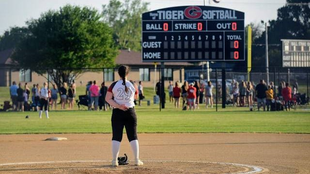 Gilbert pitcher Halli Nissen focuses on the U.S. flag during the national anthem before Tigers opened the season against Nevada on Monday night at Gilbert Middle School. Monday marked the start of the high school summer sports season in Iowa -- the first sanctioned high school sports season to begin since the COVID-19 pandemic began in March. Photo by Joe Randleman/Ames Tribune