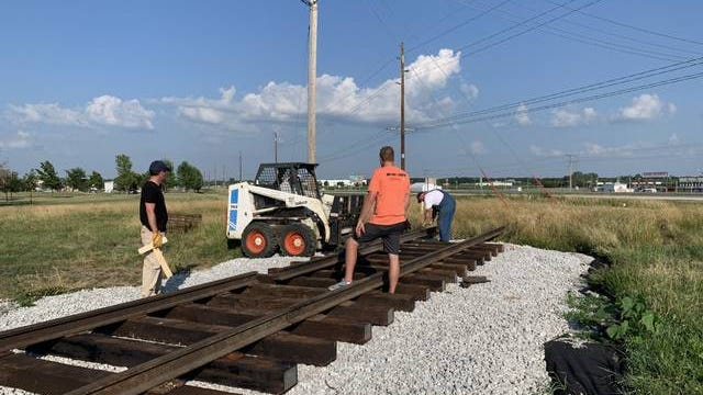 Volunteers work on train tracks at the new site of the Boone Welcome Train. Contributed photo/Boone Rotary
