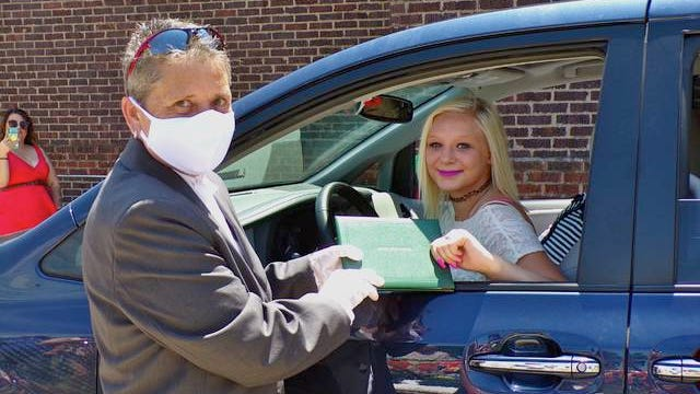 Saturday afternoon, 27 students graduated from Futures Alternative High School in Boone in a parade, drive-thru style ceremony. Pictured is school director Kim Kitterman presenting graduate Kailee Davidson with her diploma. Photo by Sara Jordan-Heintz