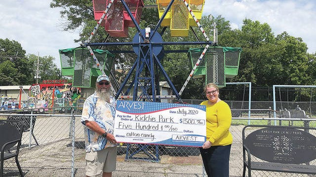 Whitney Watson, left, Arvest sales manager, presents a donation for Kiddie Park to Frank Crow, Bartlesville Playground Associate Board of Directors vice president. Courtesy