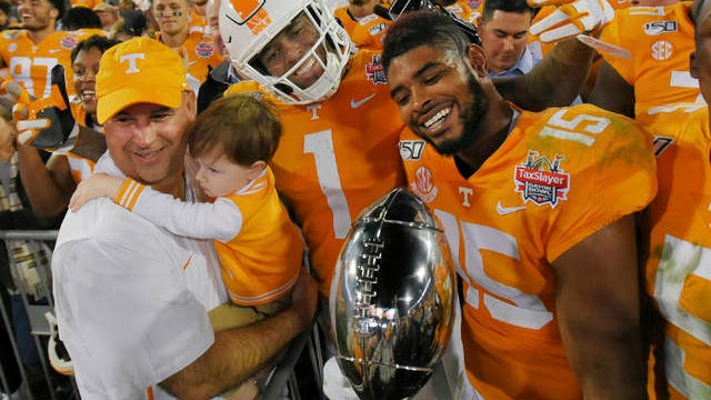 Tennessee coach Jeremy Pruitt holds his son Flynt and celebrates with seniors Marquez Callaway (1) and Jauan Jennings (15) following Thursday's 23-22 Gator Bowl win over Indiana.