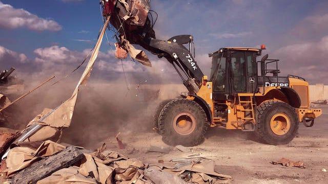 A bulldozer clears rubble and debris at Ain al-Asad air base in Anbar, Iraq,