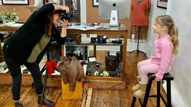 Sarah B. Gilliam, left, takes the portrait photo of Bebe Molder, daughter of Columbia Mayor Chaz Molder, during First Friday at West 7th Co. Gilliam was previewing her Maury County Portrait Series, which will become a public arts installation March 20 in the Columbia Arts District. More than 120 people participated in the First Friday event.