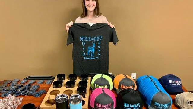 Camden Smith displays this year's Mule Day souvenirs, which include T-shirts, sweaters, blankets, mugs, pins, hats and more. Mule Day merchandise will be sold at the Mule Day Office located at Maury County Park from 9 a.m. to 5 p.m. through Friday. After Friday, the 2020 souvenirs will be sold year-round at Winning Moves, located at 1012 S. Garden St.