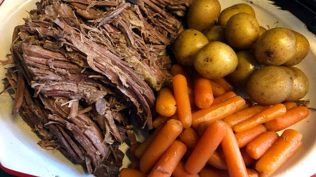 This image released by Kim Bierly shows a pot roast dinner with carrots and potatoes, made in a slow cooker. Before the coronavirus emerged, Bierly often worked late at her office and then met her husband for a quick dinner at one of the restaurants in their central Pennsylvania neighborhood. Now working from home, she's pulling out old recipes -- the kinds of things she remembers her mother making.