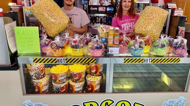 Shady Brook Cinemas staff member Alex Hyland and operations manager Sheryl Grooms hoist the theater's large $8 bags of popcorn, which it is selling along with other concessions to-go as the Columbia business adapts to changes due to the COVID-19 outbreak.