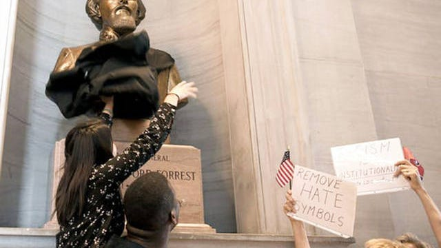 A protester tries to cover the bust of Nathan Bedford Forrest in the state Capitol in Nashville on Aug. 14, 2017.