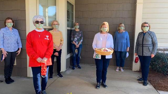 The Overton Way Ladies practice social distancing on Sue Tinker's front porch wearing the masks they all made.
