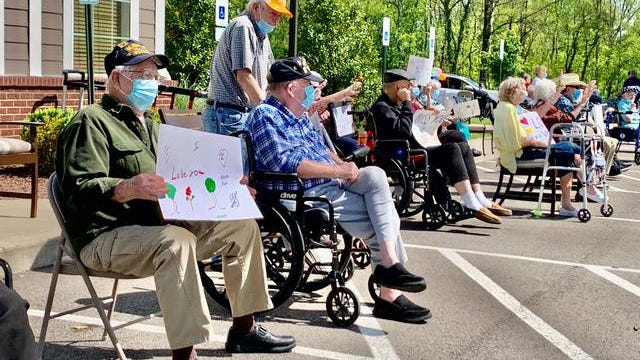 """Traditions of Spring Hill residents line up with signs to greet their family members Friday as part of a special """"resident parade,"""" where dozens of cars circled the parking lot honking and waving."""