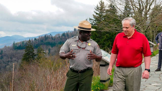 This Wednesday image from a tweet by Interior Secretary David Bernhardt, the Interior Secretary talks with Cassius Cash, the park superintendent, as he visits National Parks Service employees at Great Smoky Mountains National Park. While the Interior Secretary asked visitors to social distance when the park reopened on Saturday, neither Bernhardt nor park staff wore face masks in the photos, as they talked and walked inches apart during his visit on Tuesday.