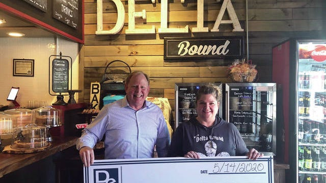 Eric DeBerry, Owner of DeBerry Insurance Agency, participating in the Erie Agents Giving Back program, presents a check for the purchase of $1,000 in gift cards to Jessica Mobley of Delta Bound, a locally owned restaurant in Spring Hill.