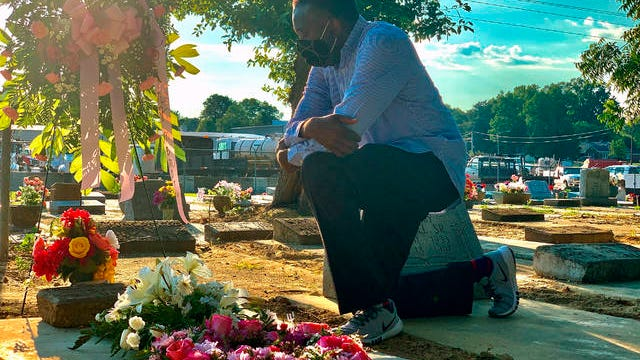 Will Boyd kneels at the grave of a family member who died after contracting the coronavirus Saturday in Montgomery, Ala. He says his family has lost multiple family members to COVID-19.