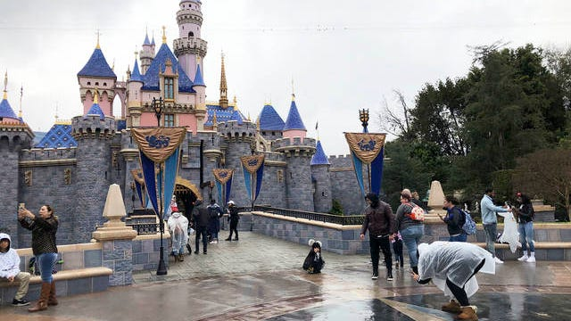 In this March 13 file photo, visitors take photos at Disneyland in Anaheim, Calif. Disney is postponing the mid-July reopening of its Southern California theme parks until it receives guidelines from the state. The company announced Wednesday an indefinite postponement for Disneyland and Disney California Adventure in Anaheim.