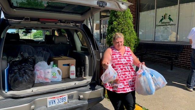 Alliance Community Pantry client Tonia Owens brings bags of food to her vehicle in this July 2020 photo. Owens has been visiting the pantry for about a year. In the trunk, the cardboard box is filled with items such as canned food and peanut butter.