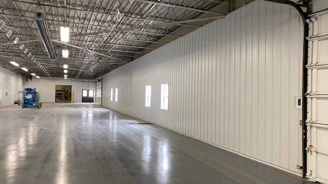New windows, doors, white steel siding and an epoxy floor seal are part of the $100,000 renovation to the D+S Distribution Nichols B facility. The clean space houses the assembly lines for Console Vault.