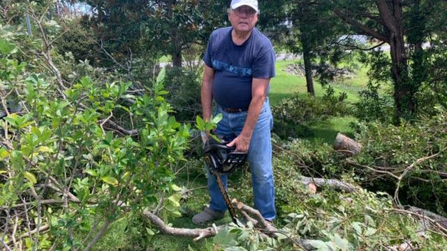 Harbour resident Jim Hampson demonstrates his prowess with a chainsaw while cleaning up his yard on Trade Winds Road after Isaias' visit.