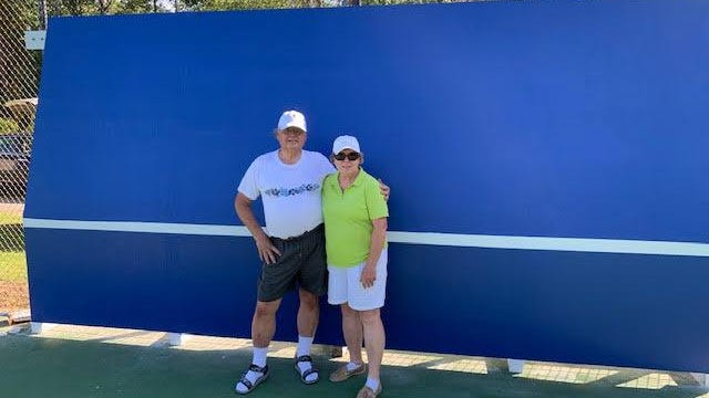 Jim and Carol Hampson are all smiles at the Red Sail tennis courts after putting the finishing touch of white net line on the new practice backboard.