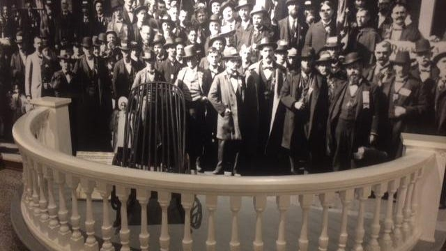 "A display in front of the McKinley Gallery at Wm. McKinley Presidential Library & Museum simulates President McKinley's 1896 ""Front Porch Campaign,"" with the background of a photograph of the presidential candidate greeting a visiting delegation."