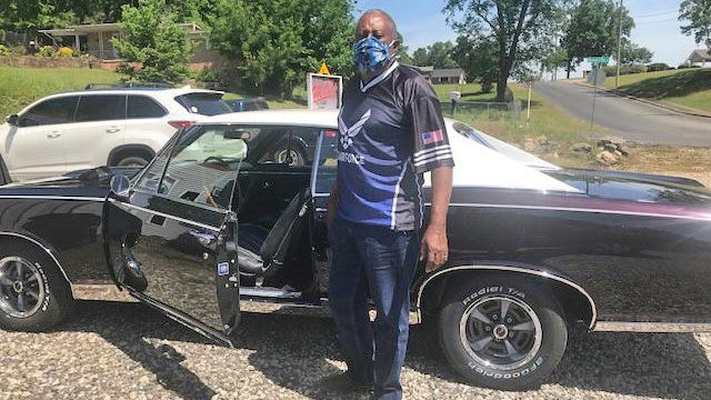 Eric Waddell stands proudly in front of his restored 1967 Pontiac GTO.