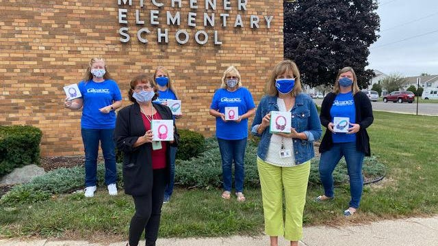 Michener Elementary School teacher Lora Wallich (front left) and principal Ann Lacasse hold some of the 100 donated headphones. Behind them are Gleaner Life Legacy Arbor representatives Christine Zeller, Robin Ginter, Deb Elliott and Julie Tison.