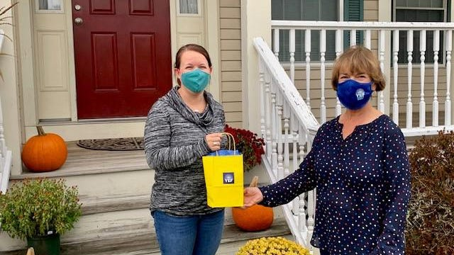 """York Education Foundation board member Julie Crafts presents the first YEF """"Appreciation Initiative"""" gift bag to Maureen Barr, educator at York Middle School."""