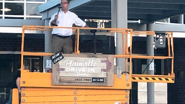 Plainville Town Moderator Luke Travis leads Town Meeting proceedings from atop a scissor lift during Plainville's drive-in style meeting on Monday at King Philip High School in Wrentham.