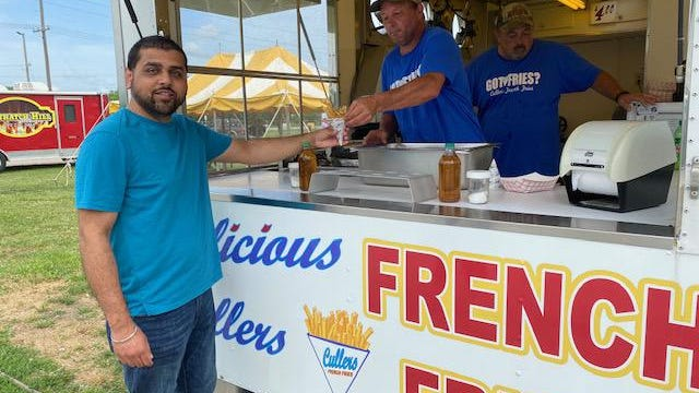 The family of Walt Landers enjoyed lunch at the Logan County Fairgrounds Monday that included French fries from Cullers. Tarak Shah is seen picking up freshly made fries from Keith and Jim Cullers. Shah, of Naperville, said his wife Carman would not miss the opportunity to eat the popular fries offered by the Cullers French Fried stand.