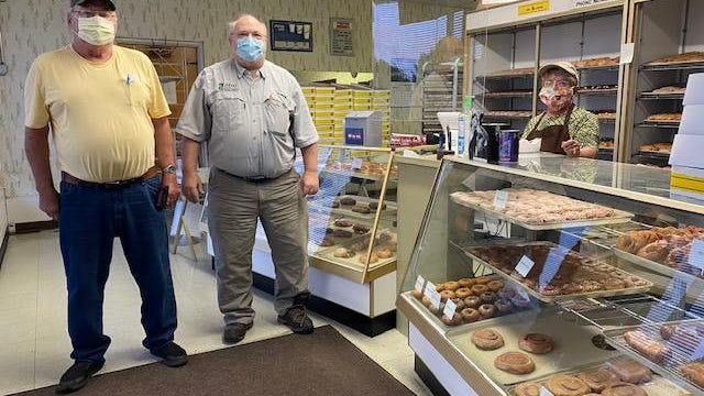 Verl Auxier and Tom Albert who arrived at Mel-o-Creme at 5 a.m. Tuesday  were the shops first customers. Yvonda Sullivan stands behind the cases filled with a variety of doughnuts for sale.