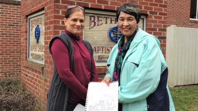 Nicola Karesh and Edith Darity show a historical image in front of Bethel Baptist Church in Rosenwald.