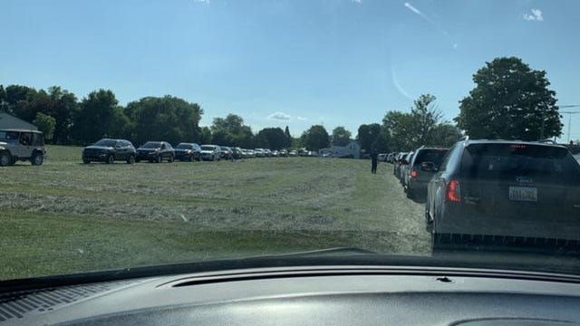 Cars, vans and pickups line up in a field behind St. Joseph Catholic Grade School in Erie for a drive-thru fish fry Friday night.