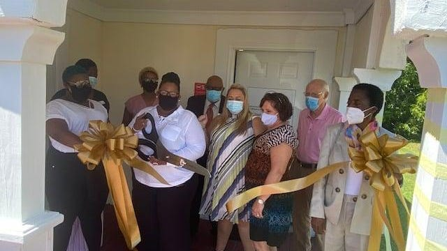 Yolanda Tennyson cuts the ribbon during a ceremony for her business, 2nd Cut, Inc., in Louisville Wednesday, July 22. 2nd Cut gives offenders and ex-offenders assistance in regaining their professional cosmetology license.