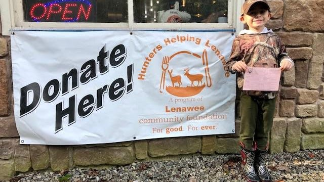 """Cole Houghton, the son of Mike Houghton, stands in front a sign promoting the """"Hunters Helping Lenawee"""" program. This year, the """"Hunters Helping Lenawee"""" program is celebrating its 10th year of providing meals for multiple organizations across Lenawee County."""