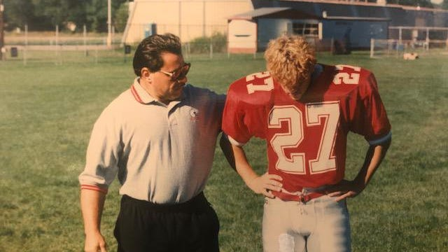 Ray Moran talks to his oldest son Michael before a game at Bedford's old football stadium.