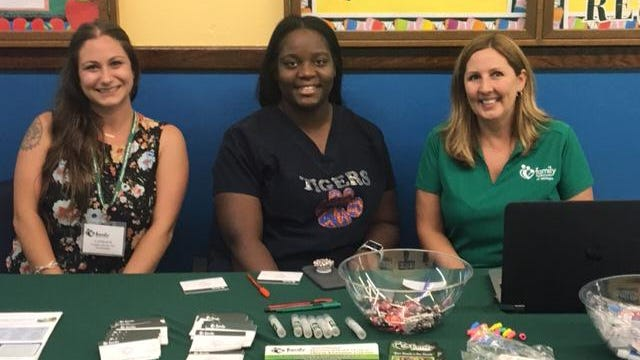 Family Medical Center school-based behavioral health staff at a table during parent-teacher conferences. From left, behavioral health specialist Candace Kovar, medical support coordinator Shachara Pullen, and director of behavioral health Jessica Parsil.