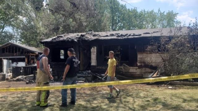 Capt. Calvin Stump (far left) from the London-Maybee-Raisinville Volunteer Fire Departments talks with his father-in-law, Sam Mills, about a fire that destroyed the Mills' home in Maybee Monday afternoon.
