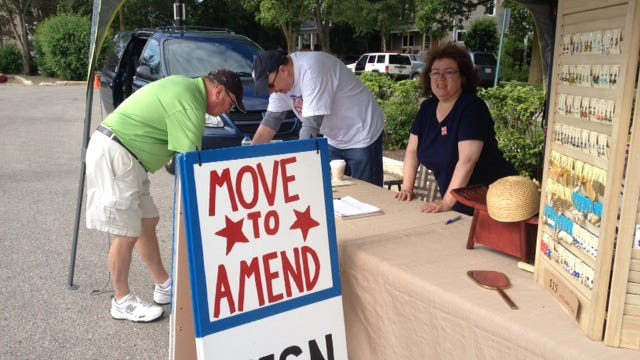 Move to Amend Fond du Lac supporters Arnie Albertz and Donna Richards seek petition signatures from a booth at the Fond du Lac Farmers Market on Saturday morning. The group needs 2,080 signatures to place a resolution on the Nov. 5 ballot.
