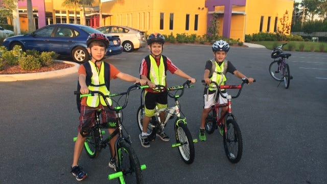 Nicholas Paez, left, Daniel Paez and Solomon Lucas arrive at Heights Elementary School on Bike to School Day.