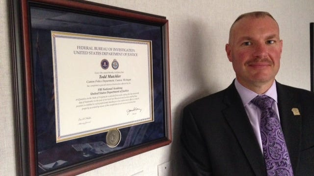 Todd Mutchler, Canton Public Safety director, stands next to the diploma he received from the FBI National Academy.