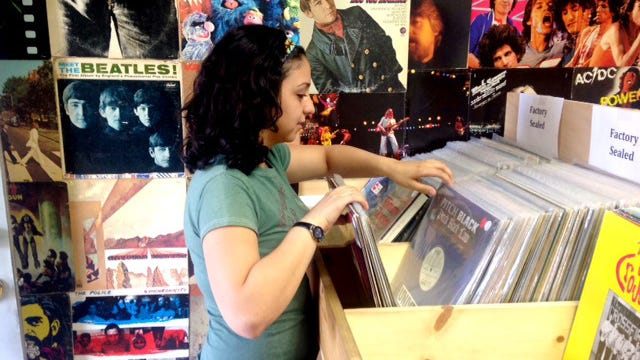 Amanda Casey, an employee at Record Revival, flips through vinyl LPs. The central Phoenix store is participating in Record Store Day today.