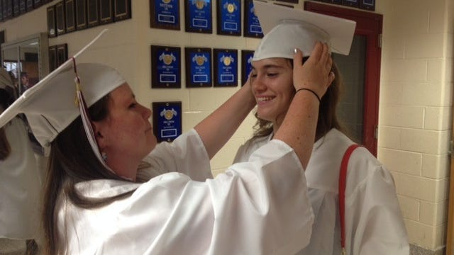 Sydney Bagley of New Paltz helps her fellow New Paltz High School graduate, Mia Potthast of Gardiner, with her cap prior to Friday night's graduation ceremony.