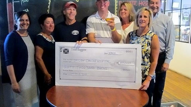 Todd Ruggere poses in Two Roads Brewery, in Stratford, Connecticut, where he drinks his last beer in his statewide Pour Tour and is given a check for $50,000 to the Smilow Cancer Hospital at Yale-New Haven. Rugere is standing alongside staffers from Smilow and Two Roads.