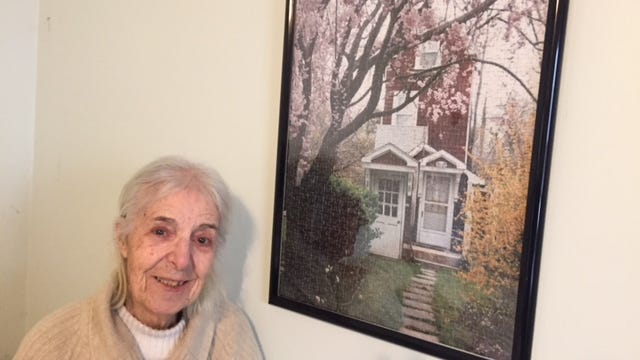 Ida Santangelo poses next to a puzzle of the Skinny House.