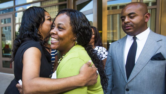 Shanesha Taylor is hugged after being released from a Maricopa County jail on July 18, 2014. The Rev. Jarrett Maupin, is at right, outside Maricopa County Superior Court in Phoenix.
