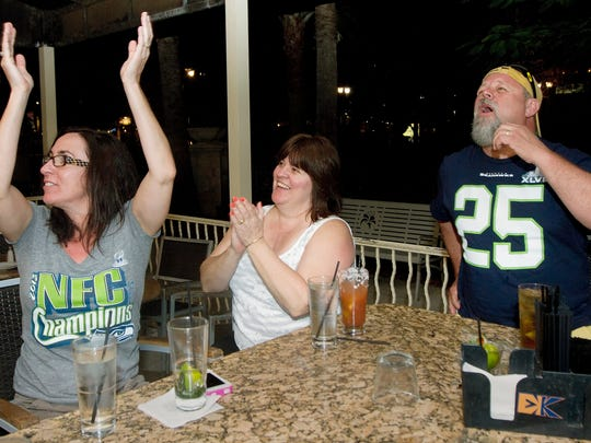 Seattle Seahawks fans Patricia Chaulk, left, Julie MacInnis and Dean Chaulk celebrate a Seattle touchdown while watching NFL Super Bowl XLVIII at Bar Louie in Fort Myers.