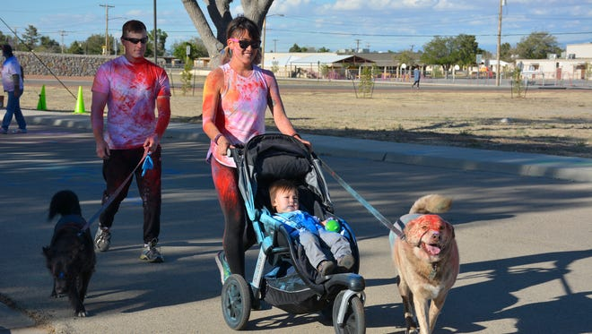 Joshua Fosher and his wife Nalani walk with their son and dogs during the April 1, Color Run held at WSMR. WSMR community members are encouraged to participate in the IMCOM walking-challenge for bragging rights among 16 other garrison and headquarters teams participating in the challenge.