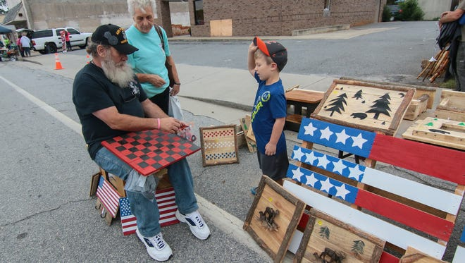 Steve Haynes, left, sells Caden Eliopoulos, right, of Anderson a wooden checker board Saturday near Caden's grandmother, Sharon Mauldin.
