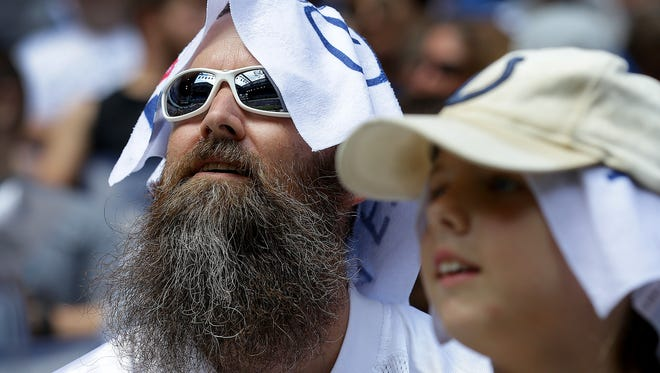 Danny Tippit and daughter Grace, from Indianapolis, keeps their head cool as they watch the Colts practice during the first day of Colts preseason training camp Sunday, July 30, 2017, afternoon at Lucas Oil Stadium.